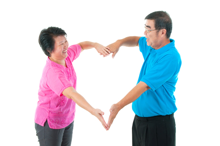 couples in love: Asian senior couple making heart shape with hands Stock Photo