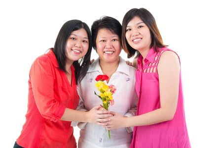 old asian: Asian woman receiving carnation flower from daughters on mothers day