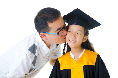asian family: Asian girl in graduation gown kissed by her father