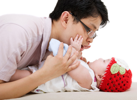 six months: Asian father playing with his six months old baby girl
