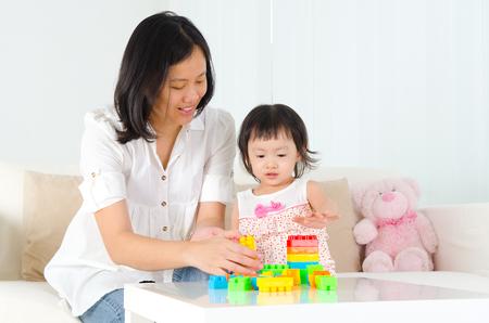 madre e hija: Asia madre y el niño jugando bloque de construcción