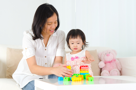 relationship mother and daughter: Asian mother and kid playing building block