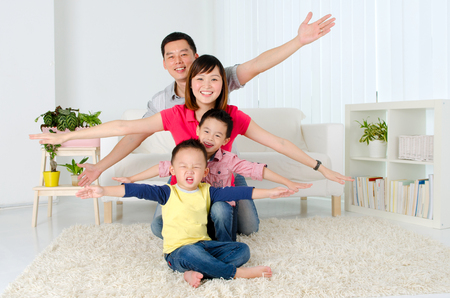 Indoor portrait of asian family open their arms Stockfoto
