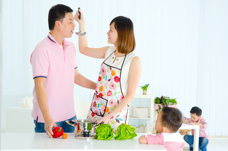 asian wife: Asian husband and wife cooking in the kitchen and kids are doing schoolwork in the living room