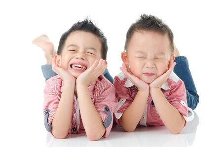 niños sonriendo: Encantadores muchachos asiáticos que mienten en el suelo Foto de archivo