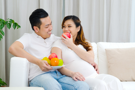 family indoors: Asian pregnant woman eating an apple and looking at her husband