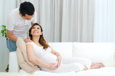 young asian couple: Asian pregnant woman lying on sofa and looking at her husband