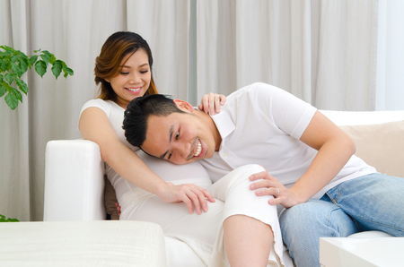 Asian man listening to his pregnant wife's stomach