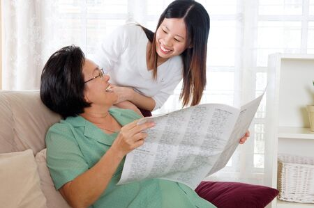 senior asian: Asian senior woman holding newspaper and talking with daughter Stock Photo