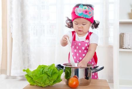 Kleines asiatisches Mädchen, das Spaß mit dem Kochen Standard-Bild - 50057065