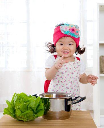 niños comiendo: Niña asiática que se divierte con la cocina