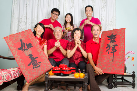 wishful: Asian family celebrate chinese new year, family member hold bunting with the word of auspicious and wishful in chinese character