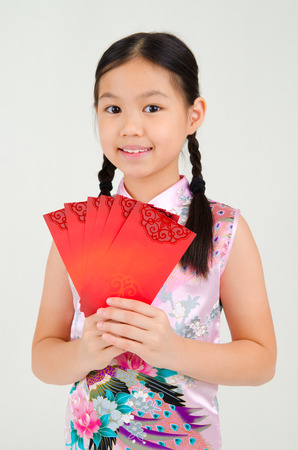red packet: Asian girl in traditional chinese costume, cheongsam holding red packet. Chinese new year concept. Stock Photo