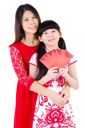 red packet: Asian woman and daughter in traditional chinese costume and holding red packet. Chinese new year concept.