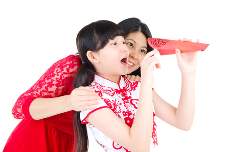 red packet: Asian woman and daughter looking into the red packet with surprise expression. Chinese new year concept. Stock Photo