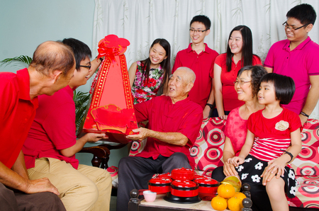 hamper: Grandson presenting gift hamper to grandfather on chinese new year. Stock Photo