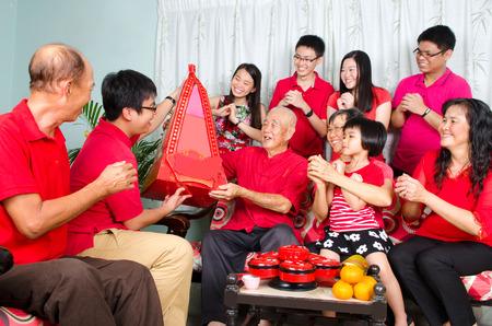 Grandson presenting gift hamper to grandfather on chinese new year. Standard-Bild
