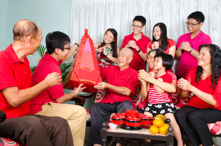 three wishes: Grandson presenting gift hamper to grandfather on chinese new year. Stock Photo