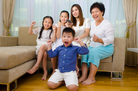 fans: Asian three generations family watching television and shouting on their home side in a sporting competition Stock Photo