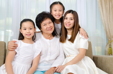 Indoor portrait of cheerful asian senior woman together with daughter and grandchildren