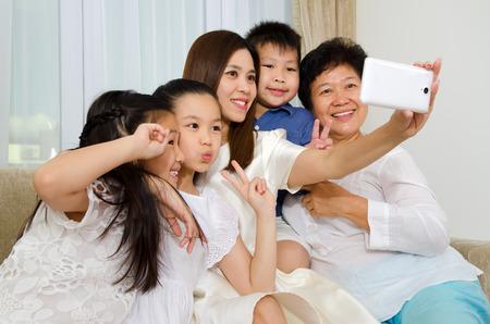 three generations: Asian three generations family taking photo of themselves using handphone Stock Photo