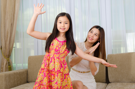 adorable child: Asian woman looking at her daughter dancing happily