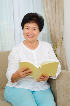 asian lady: Indoor portrait of asian senior woman reading book