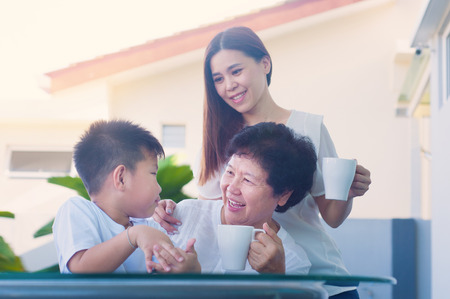 Asian senior woman relax in the garden together with daughter and grandchild