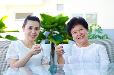 home life: Asian senior woman and daughter enjoying tea time