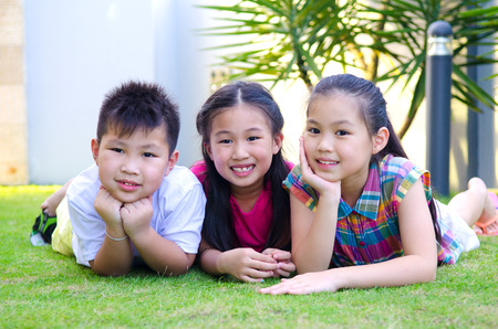 asia children: Outdoor portrait of asian kids lying on the grass