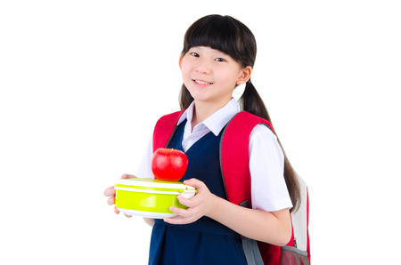 Asian primary school girl holding lunch box. Healthy eating concept for schoolchild. Stock Photo