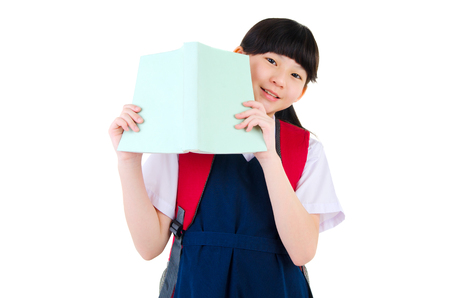 southeast asian: Asian primary school girl holding a book isolated on white background