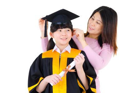 toga y birrete: Madre asiática ajustando traje de graduación de su hija