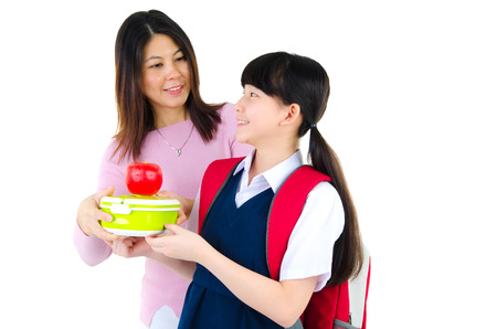 Asian primary school girl receiving healthy lunch box from mother Stock Photo