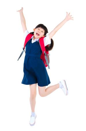 uniforme escolar: Emocionado asiática niña de la escuela primaria saltar aislado en fondo blanco