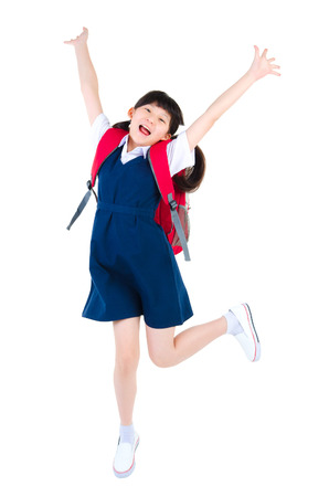 Excited asian primary school girl jump up isolated on white background