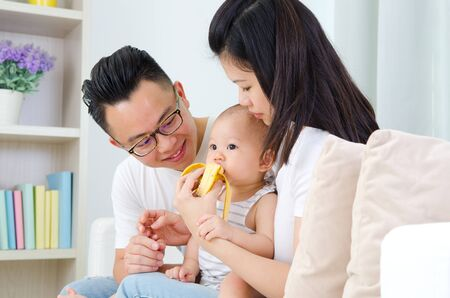 mom dad: padre asiático alimentar a su bebé con el plátano Foto de archivo