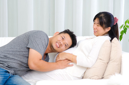 embarazada feliz: cheerful asian man listening to his pregnant wifes belly