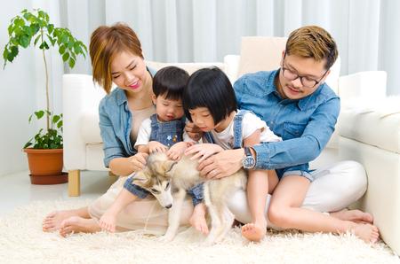 Familia asiática jugando con el animal doméstico en la sala de estar