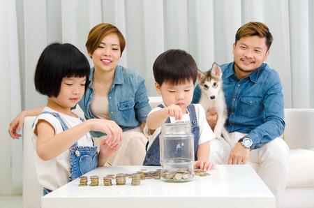 convivencia familiar: niños asiáticos que pone monedas en el frasco de vidrio. Foto de archivo