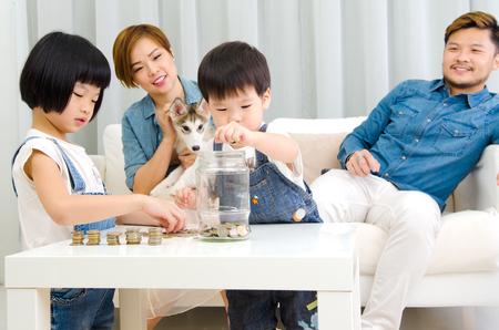 convivencia familiar: niños asiáticos poniendo monedas en botella de vidrio. concepto de ahorro de dinero. Foto de archivo