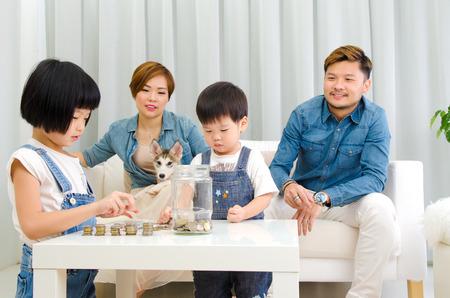 Asian kids calculating coins. Money saving concept.