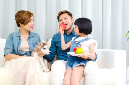 heathcare: Cute asian girl feeding her father with apple Stock Photo