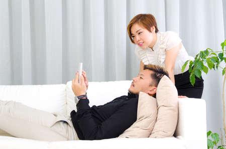 pareja en casa: Pares asiáticos que miran telefono Foto de archivo
