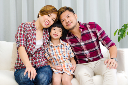 family sofa: Indoor portrait of beautiful asian family sitting on sofa