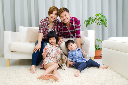 asian family home: Asian family having fun time with puppy at home Stock Photo