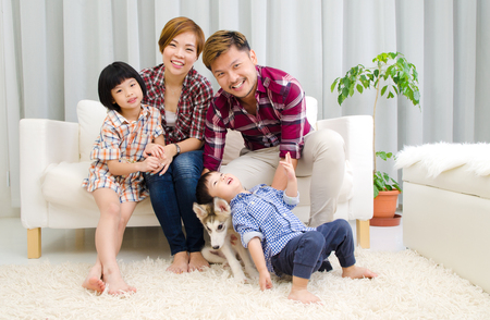 korean man: Indoor portrait of asian family having fun with their puppy