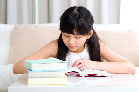 thai student: Beautiful asian girl reading book at home