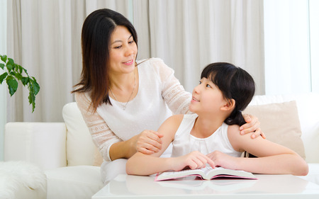 Asian mother talking to her daughter Stockfoto