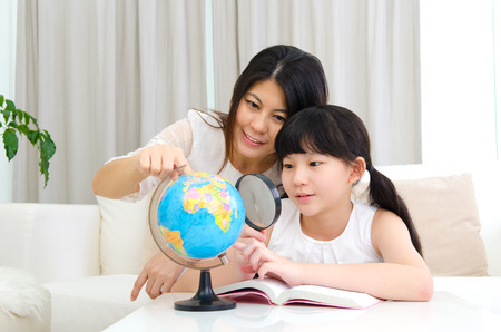 Asian mother and daughter looking at the globe